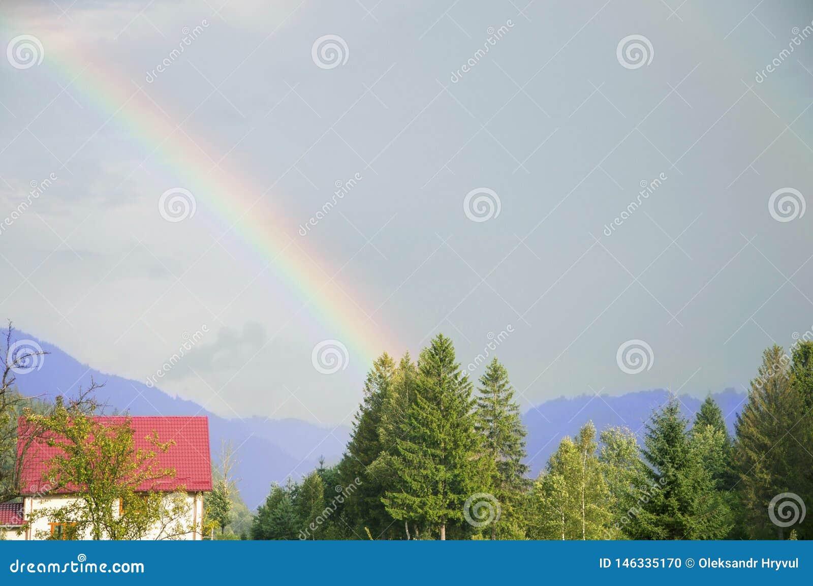 Paisaje de la monta?a Arco iris y rayos de sol sobre pueblo