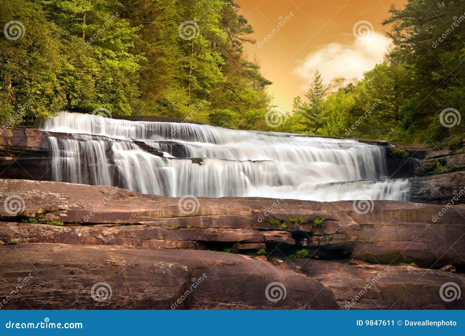 Paisaje de la naturaleza de las cascadas en puesta del sol de las montañas