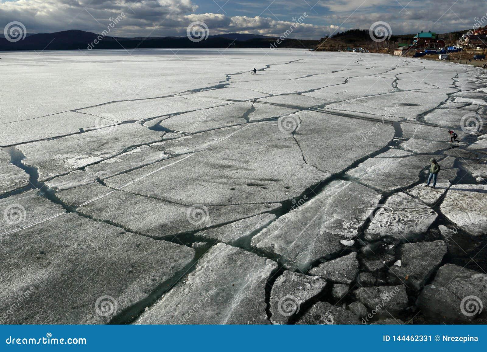 Paisaje de la primavera con la deriva del hielo en el lago y los ciclistas y la gente que montan a lo largo de él
