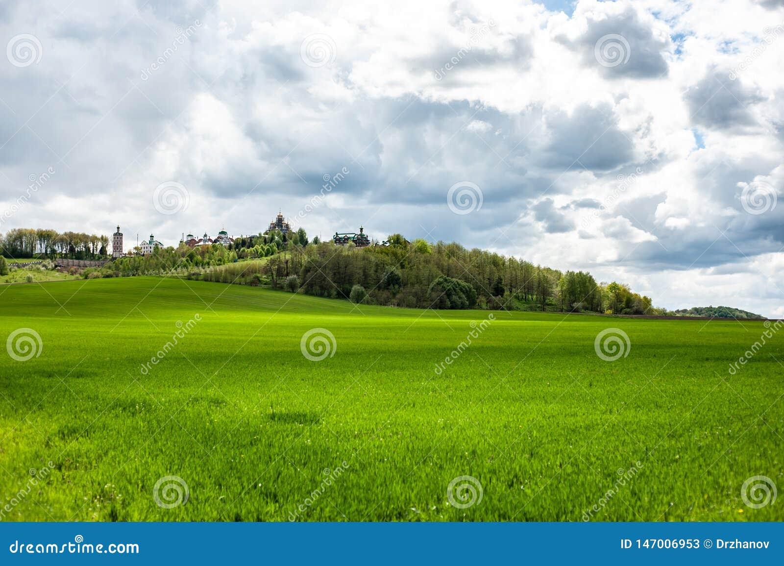 Paisaje de la primavera con la hierba verde, las colinas y los árboles, cielo nublado