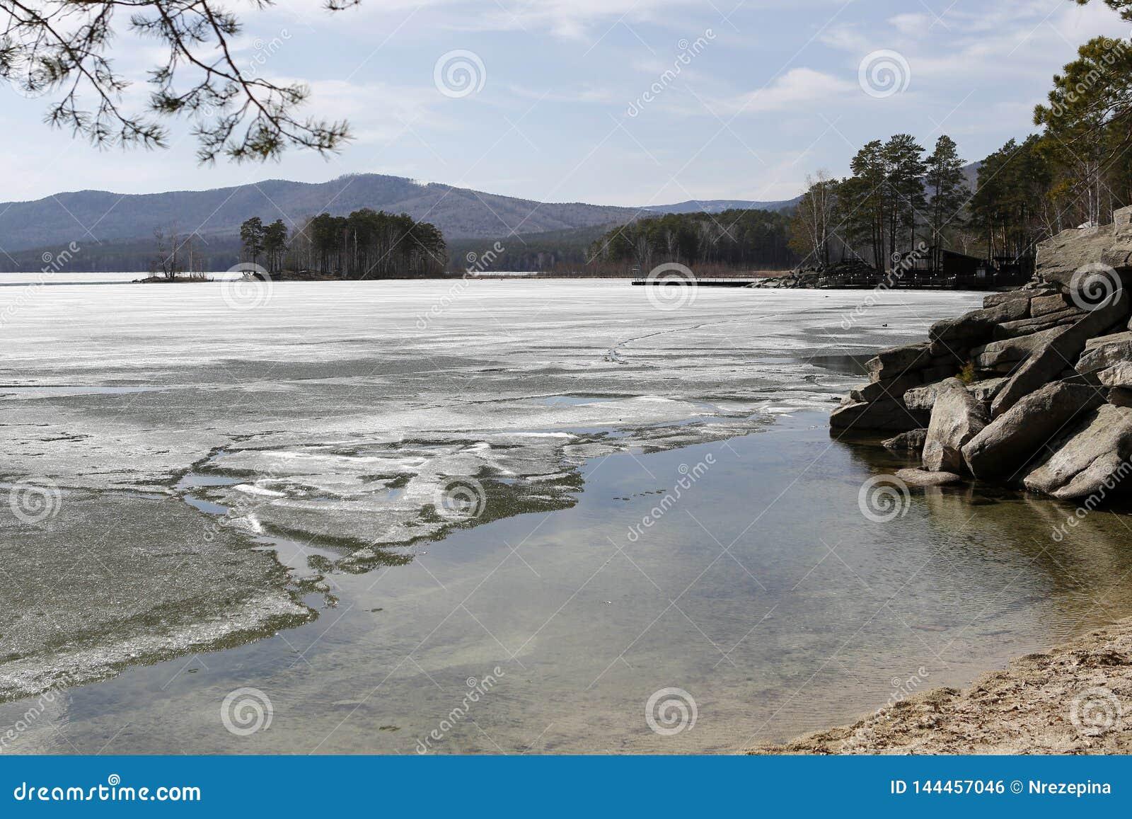 Paisaje de la primavera en un lago con las orillas