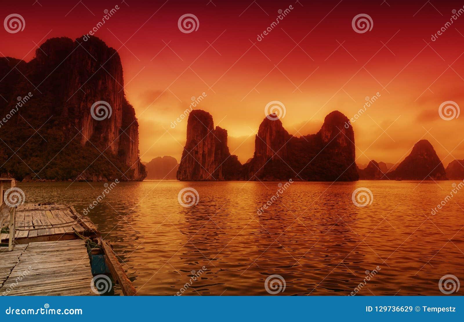 Paisaje de Vietnam de la bahía de Halong bajo puesta del sol anaranjada