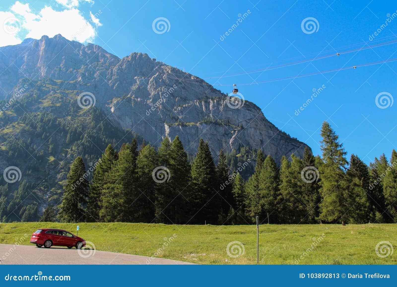 Paisaje del paisaje con el bosque, el macizo de la montaña y el teleférico verdes Malga Ciapela, Véneto, Italia