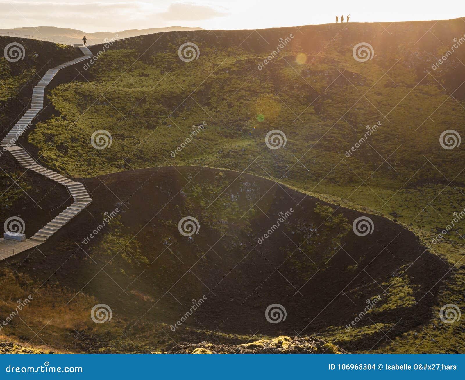 Paisaje del cráter volcánico cubierto de musgo verde enorme, o caldera, y escaleras de madera con los turistas retroiluminados