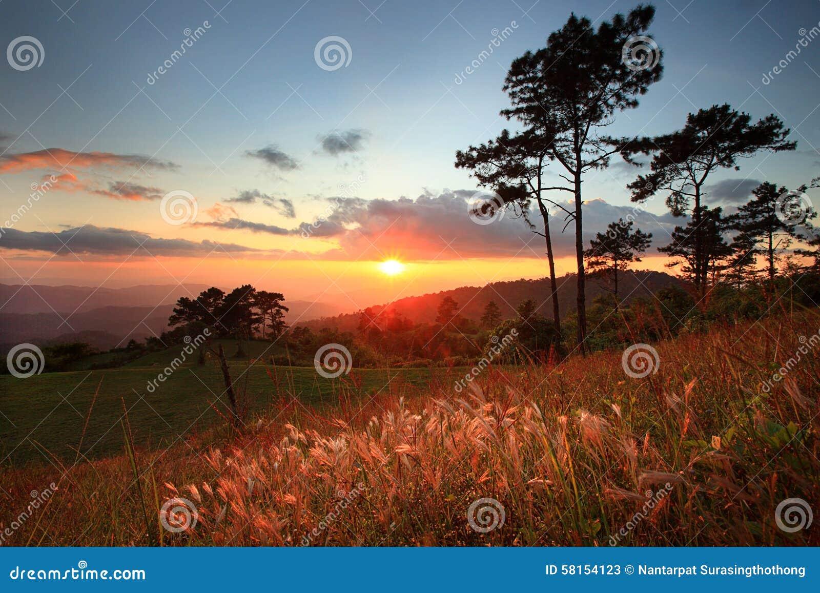 Paisaje hermoso de la puesta del sol con la montaña y la nube agradable