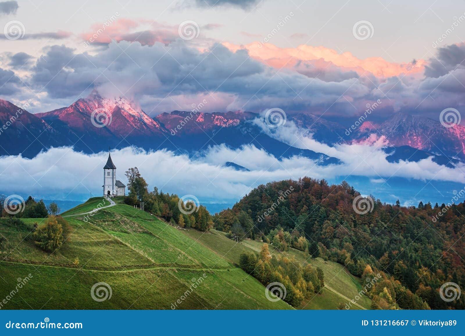 Paisaje hermoso de la salida del sol de la iglesia Jamnik en Eslovenia con el cielo nublado