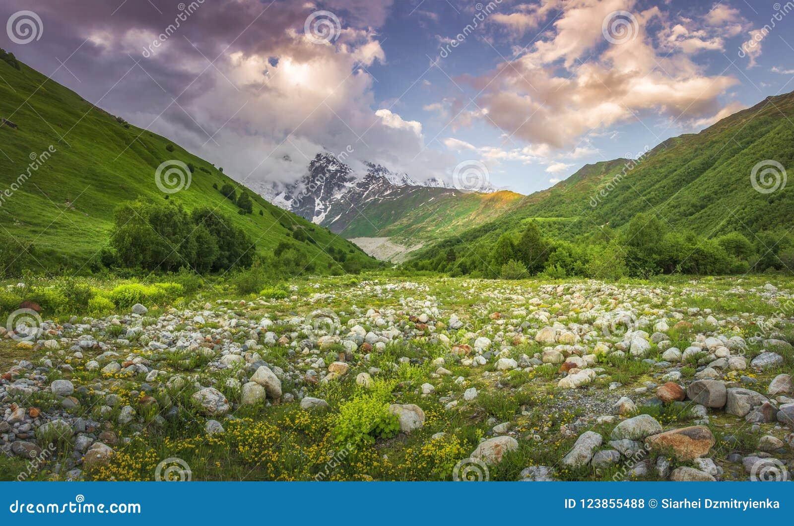 Paisaje hermoso de las montañas en la puesta del sol Nubes rosadas en cielo sobre pico de montaña nevoso