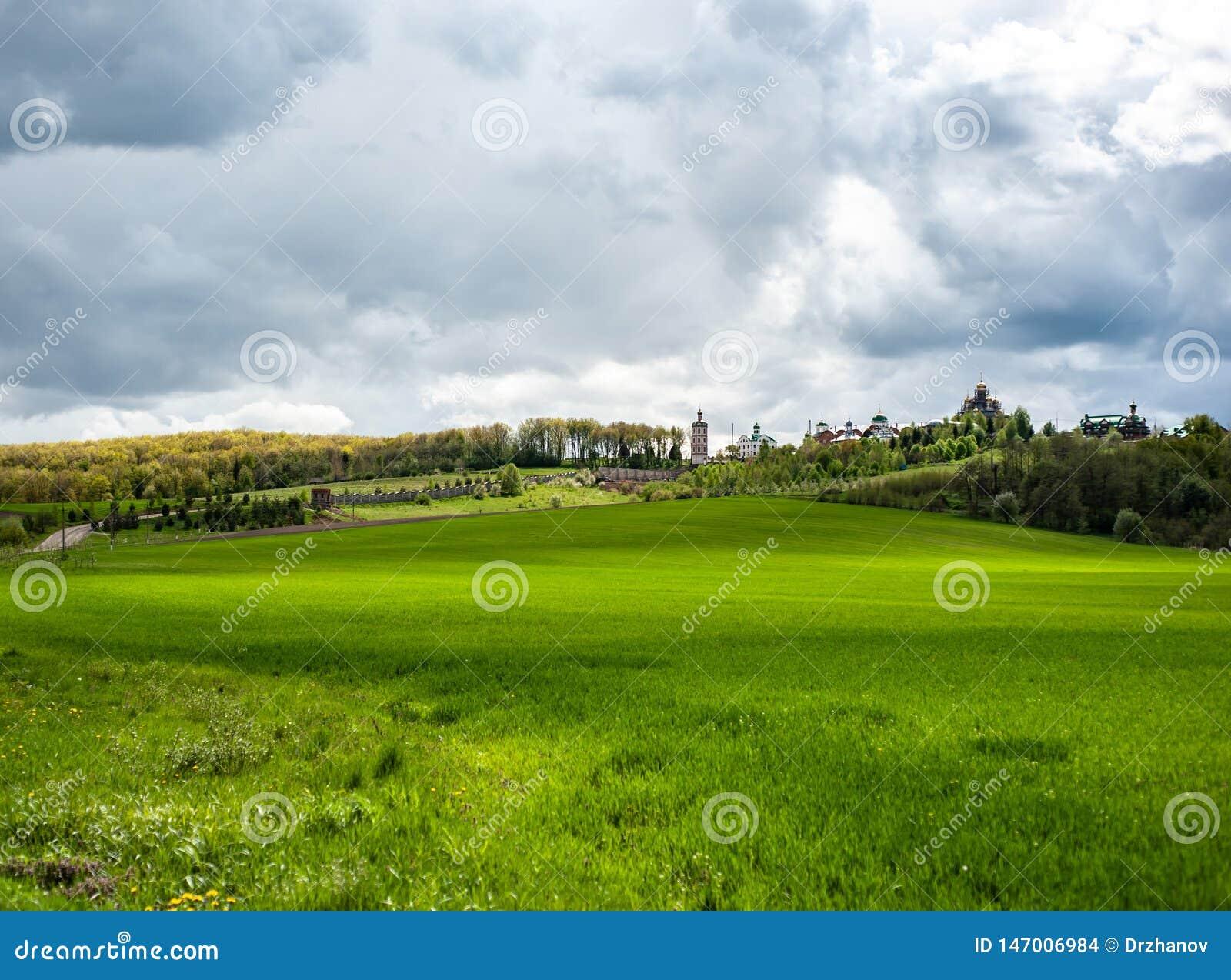 Paisaje llamativo con la hierba verde de la primavera, las colinas y los árboles, cielo nublado