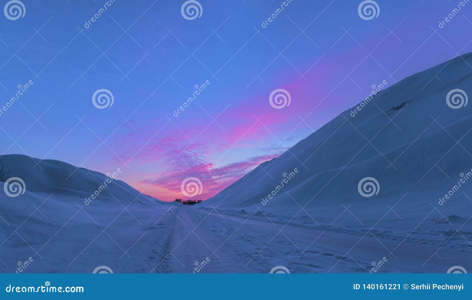Paisaje magnífico de la nieve acumulada por la ventisca en fondo de la puesta del sol en Krivoy Rog, Ucrania Montañas del inviern