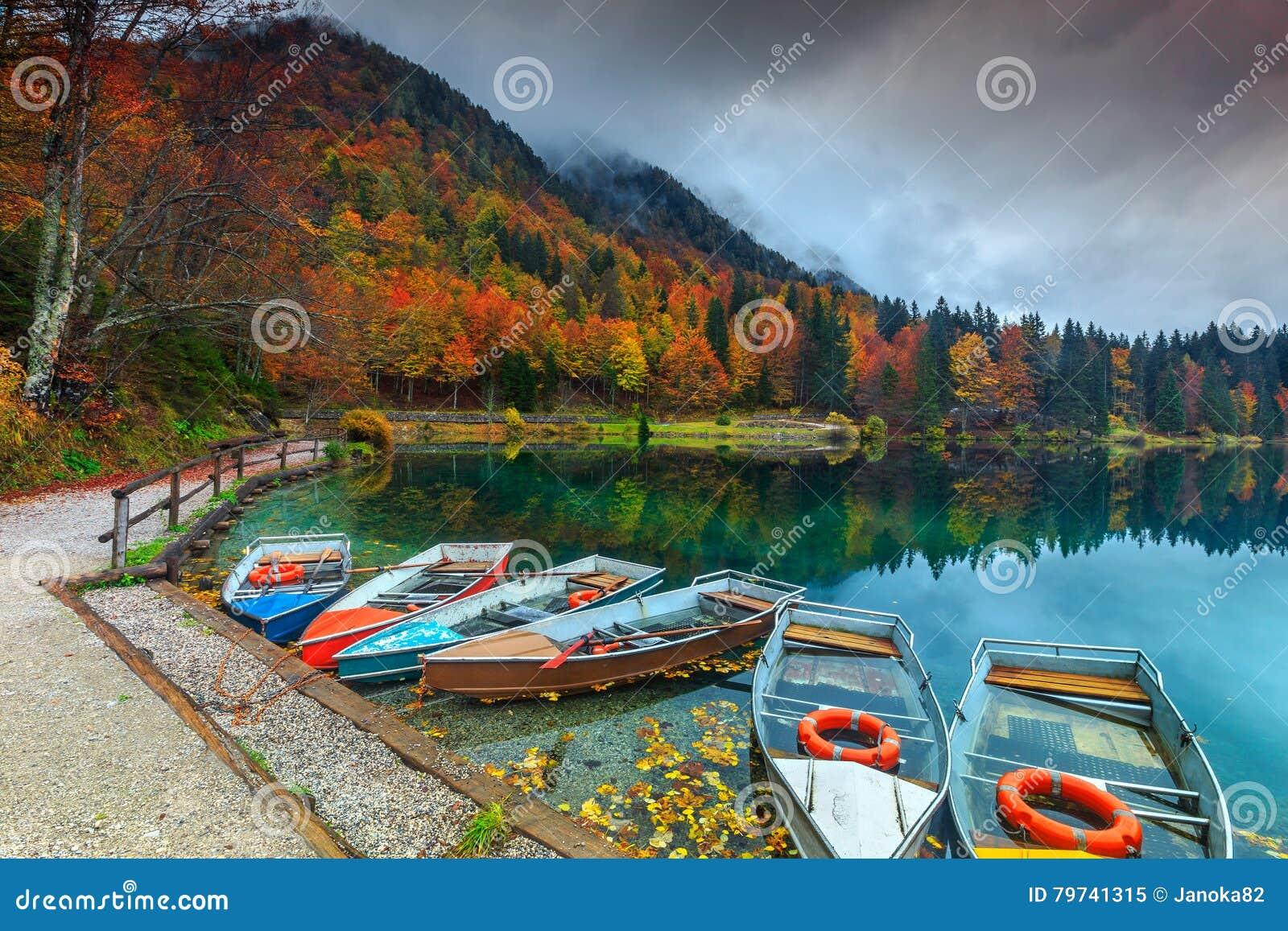 Paisaje maravilloso y barcos coloridos, lago Fusine, Italia, Europa del otoño