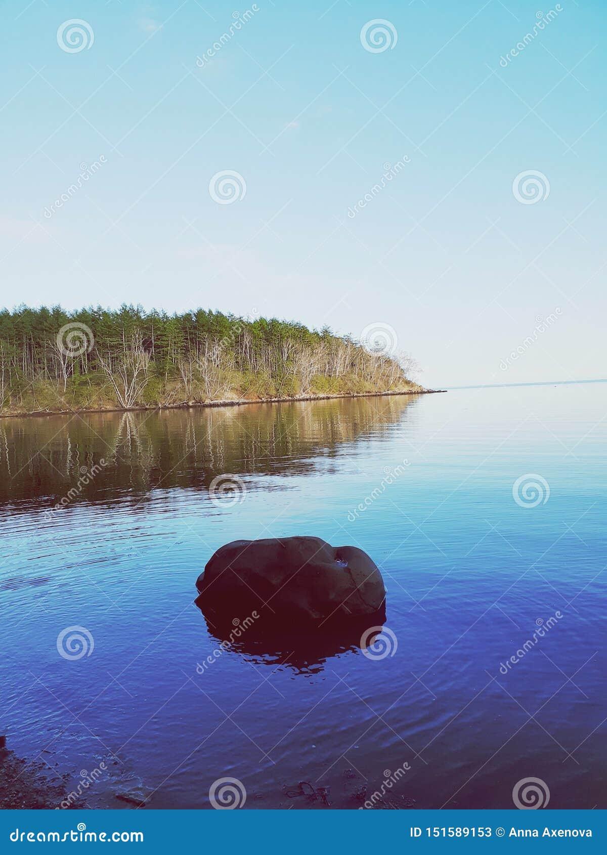 Paisaje marino hermoso en la puesta del sol de un día de verano con una piedra en el primero plano