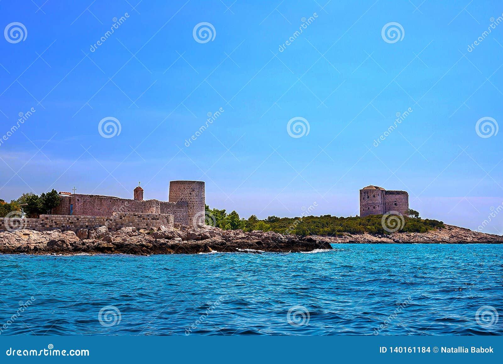 Paisaje marino increíble Torre vieja en una orilla rocosa por el mar, bahía de Boka-Kotor,