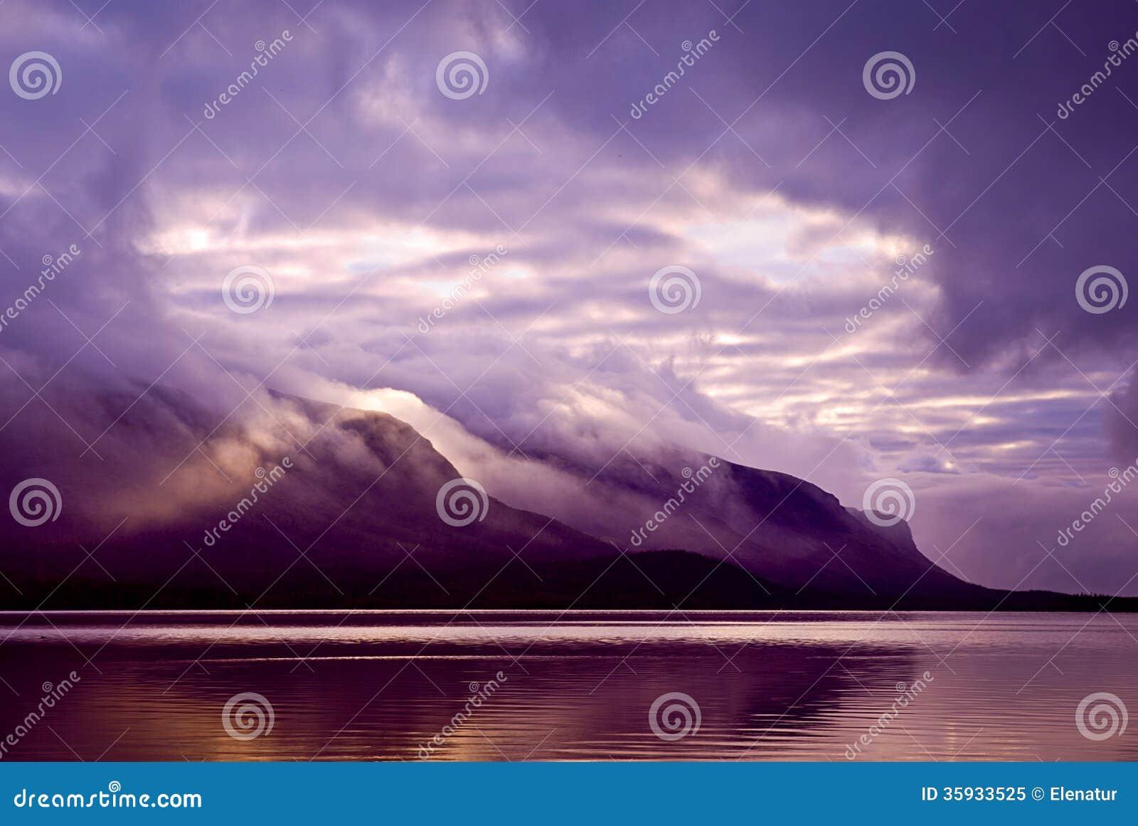 Paisaje. Montañas y lago en niebla por mañana con la cuesta púrpura