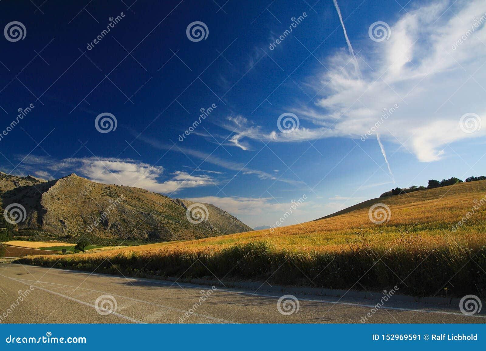 Paisaje rural bajo formaciones dramáticas de la nube del cielo en los altos llanos de Sierra Nevada