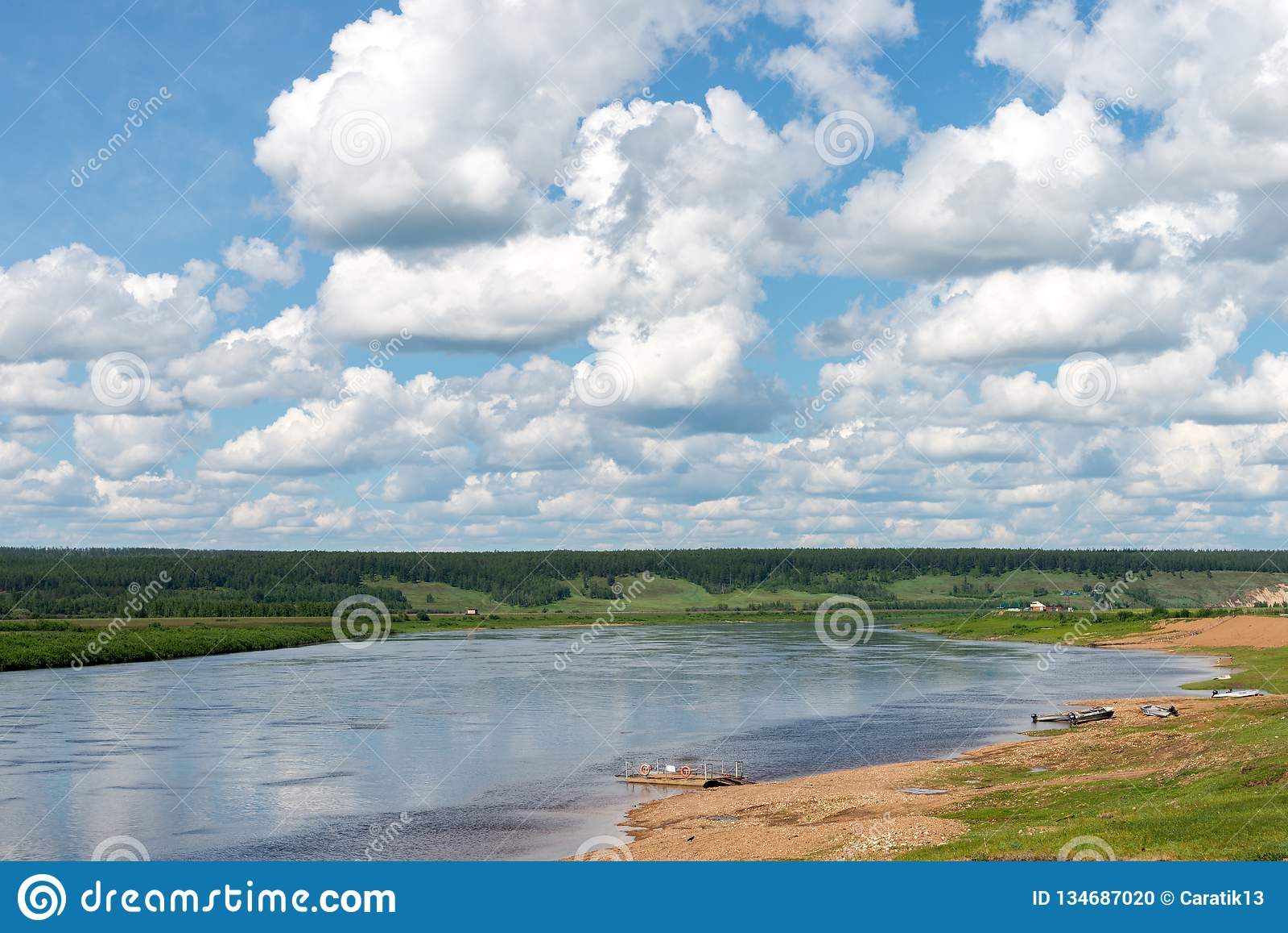Paisaje rural con el pueblo y el río en el día nublado del verano