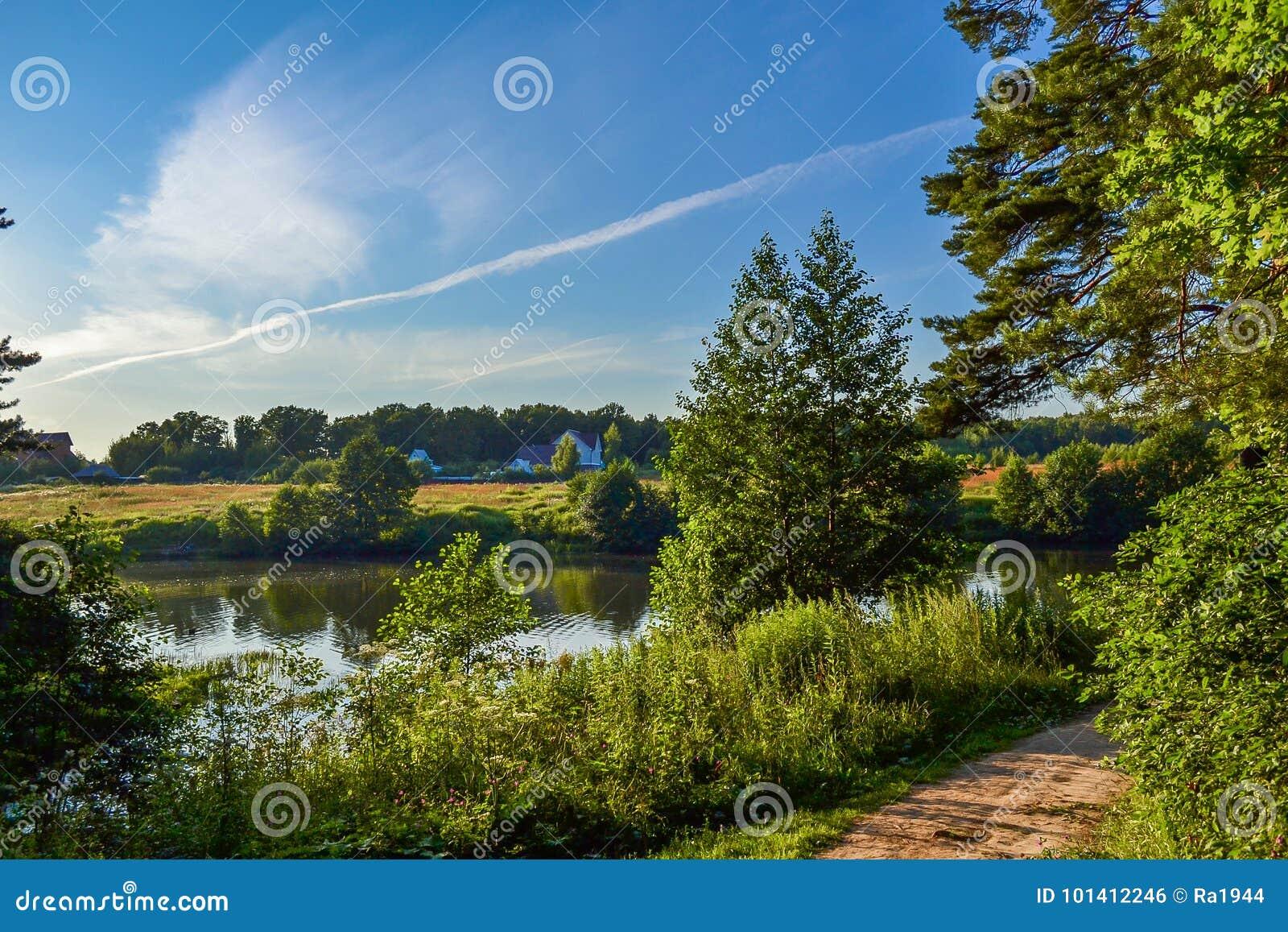 Paisaje rural hermoso Casa residencial cerca del río Árboles con verdor brillante y el cielo azul con las nubes hermosas Verano
