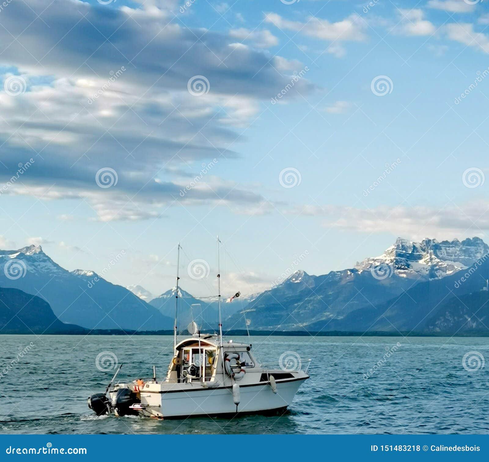 Paisaje sobre las abolladuras du Midi del lago Lemán y las montañas suizas con un barco de pesca como firstground