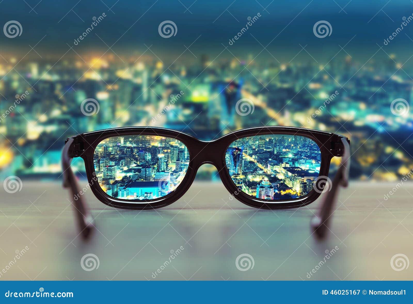 Paisaje urbano de la noche enfocado en lentes de los vidrios