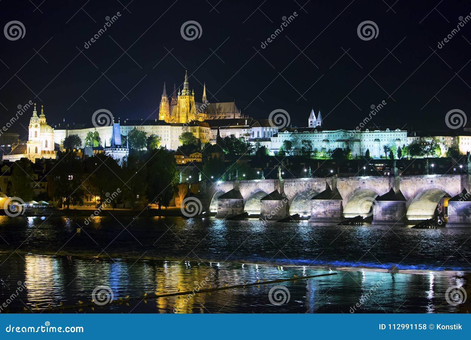 Paisaje urbano hermoso de Praga en la noche con Charles BridgeKarluv Most sobre el castillo del río y de Praga de Moldava, Repúbl