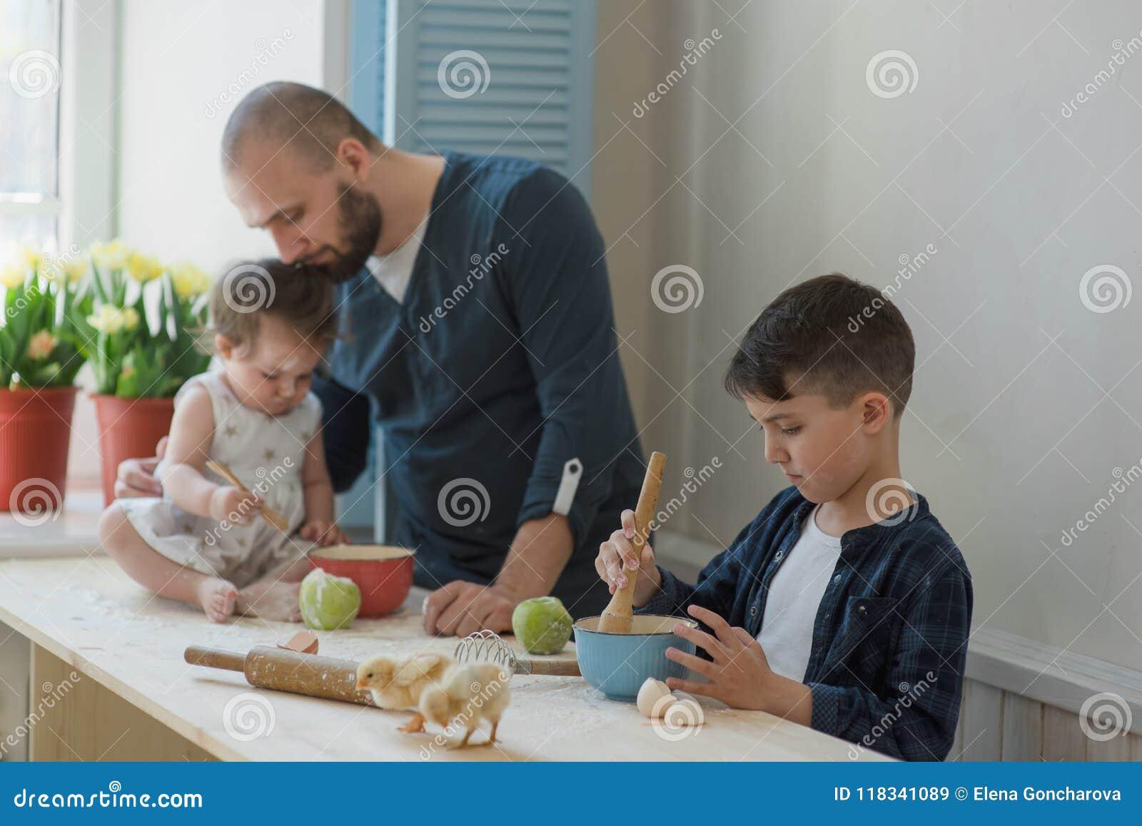 Paizinho com seus filho e filha pequenos que cozem junto