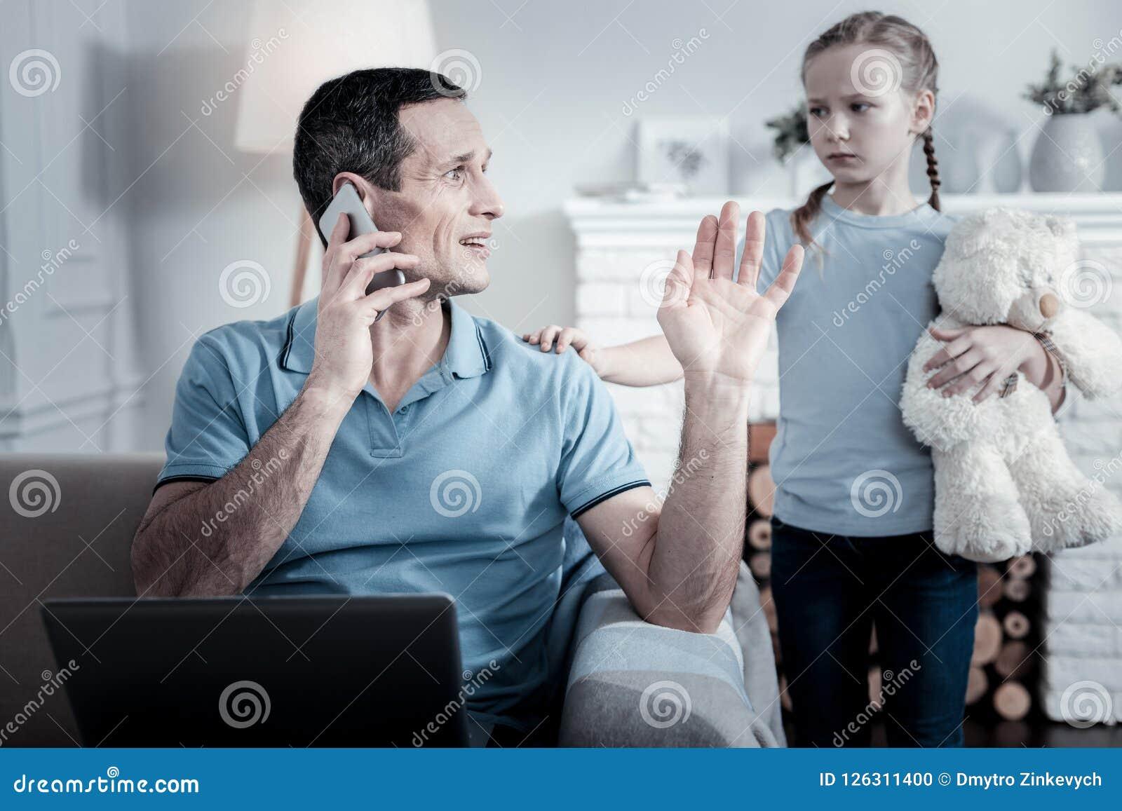 Paizinho indiferente que fala no telefone celular