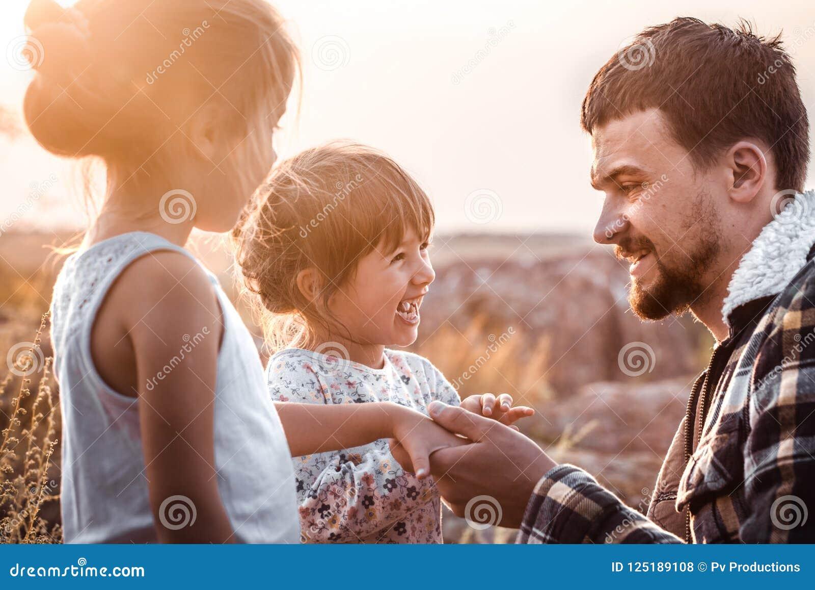 Paizinho que joga com as duas filhas bonitos pequenas