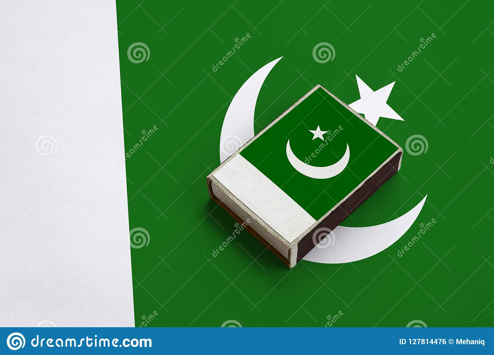 Pakistan flag is pictured on a matchbox that lies on a large flag