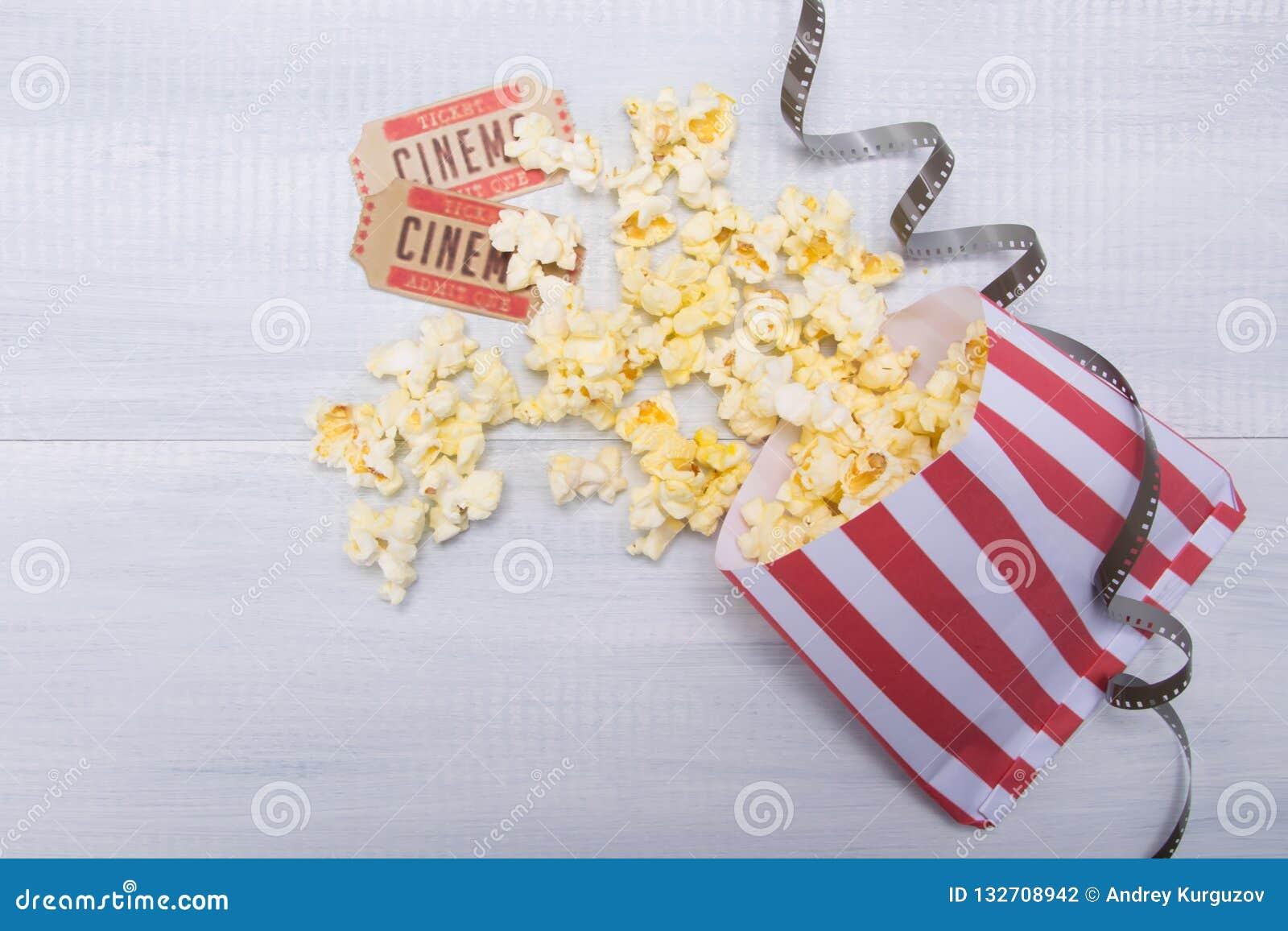 Pakunek z rozrzuconym popkornem, dwa filmów biletami i filmem, na świetle - szary tło