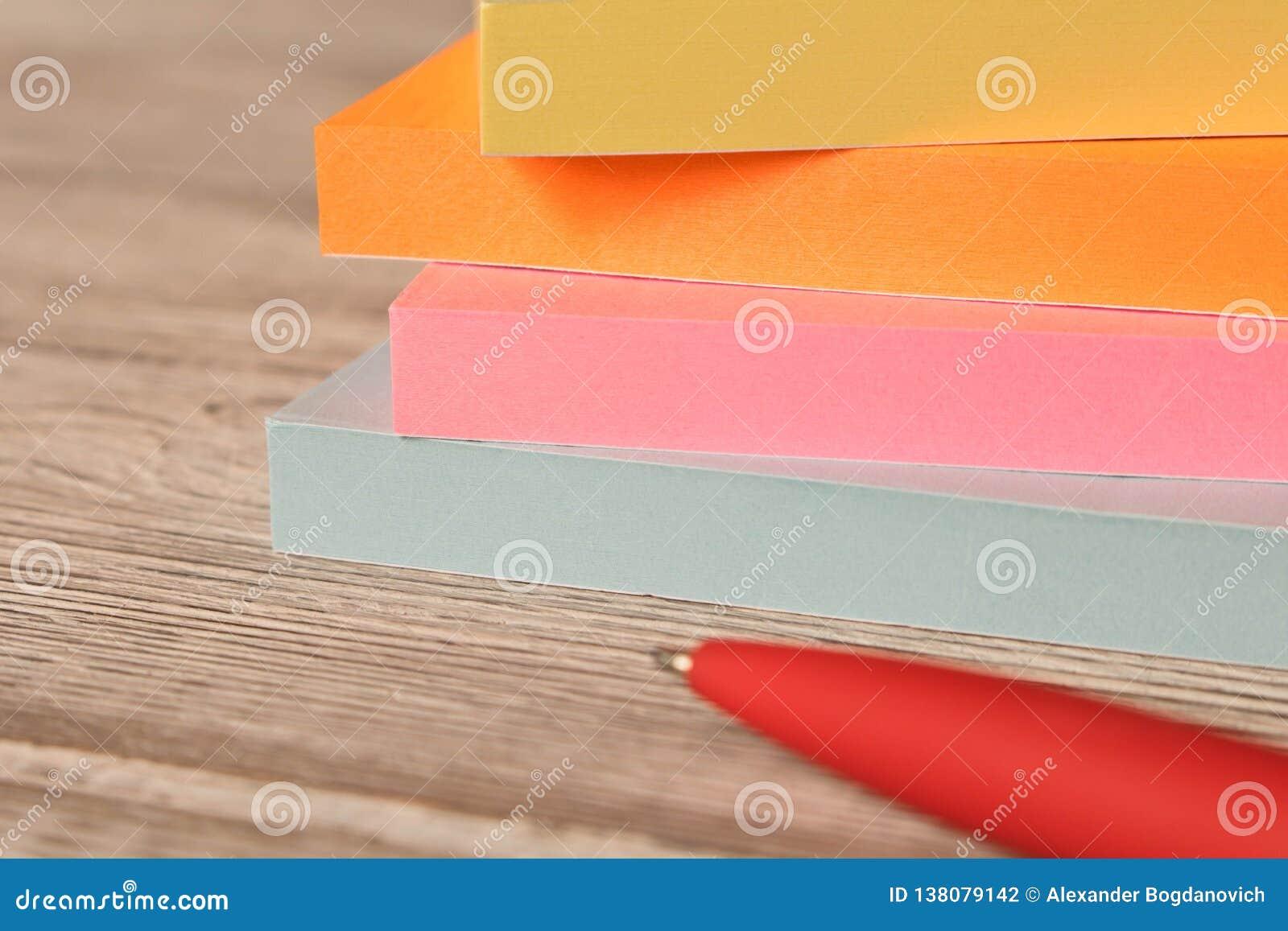 Pakunki kolorowi majchery dla notatek i pióro na drewnianym stole