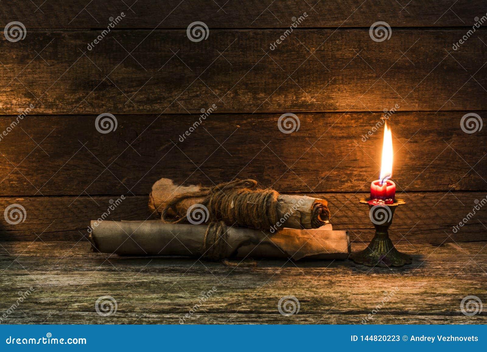 Palący dokumenty i płonąca świeczka na starym, będącym ubranym stole,