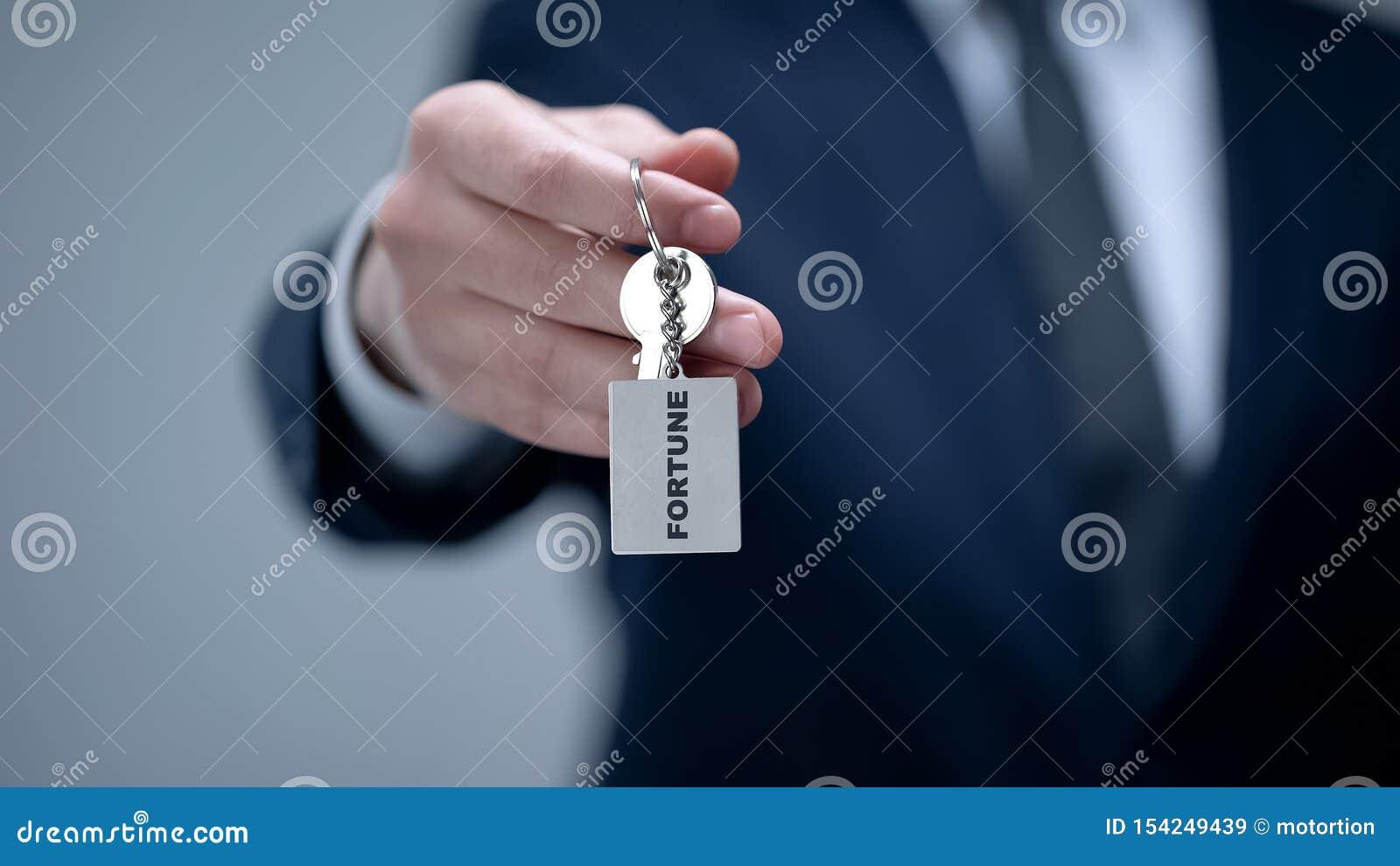Palabra de la fortuna en llavero en la mano del hombre de negocios, secreto dominante del futuro acertado