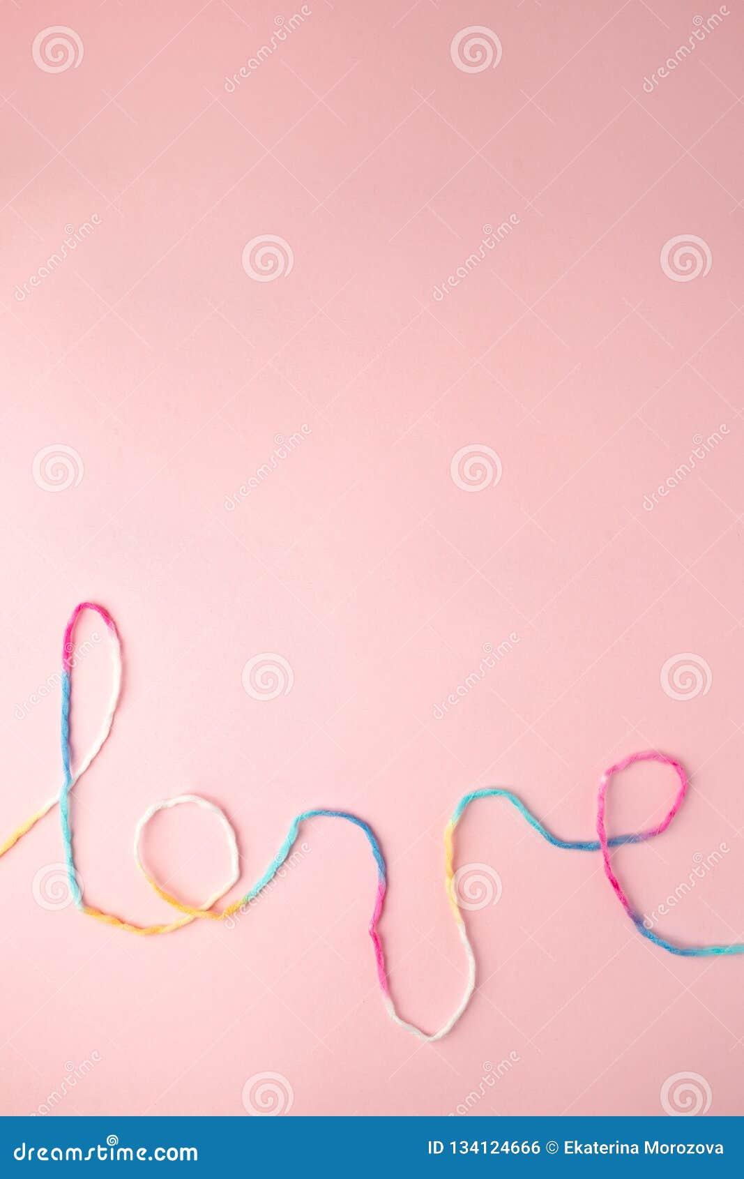 Palabra del amor escrita con las letras, concepto y el fondo de lana del hilo para el día de tarjeta del día de San Valentín, esp