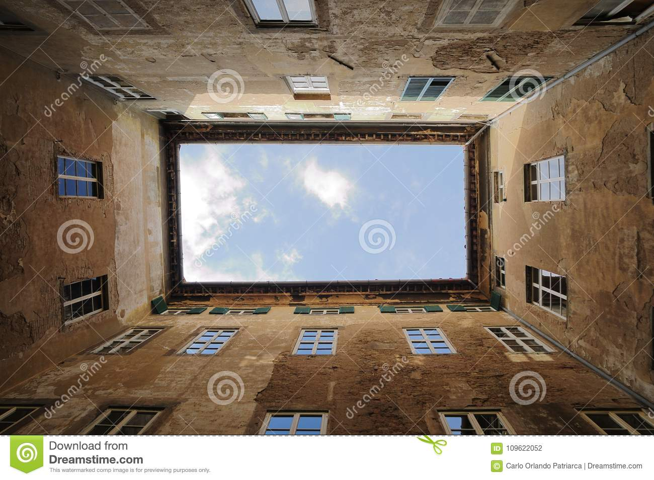 Palace courtyard in Cortona, Tuscany Italy. Vertical and perspective photo of the ancient exterior walls with cloudy sky