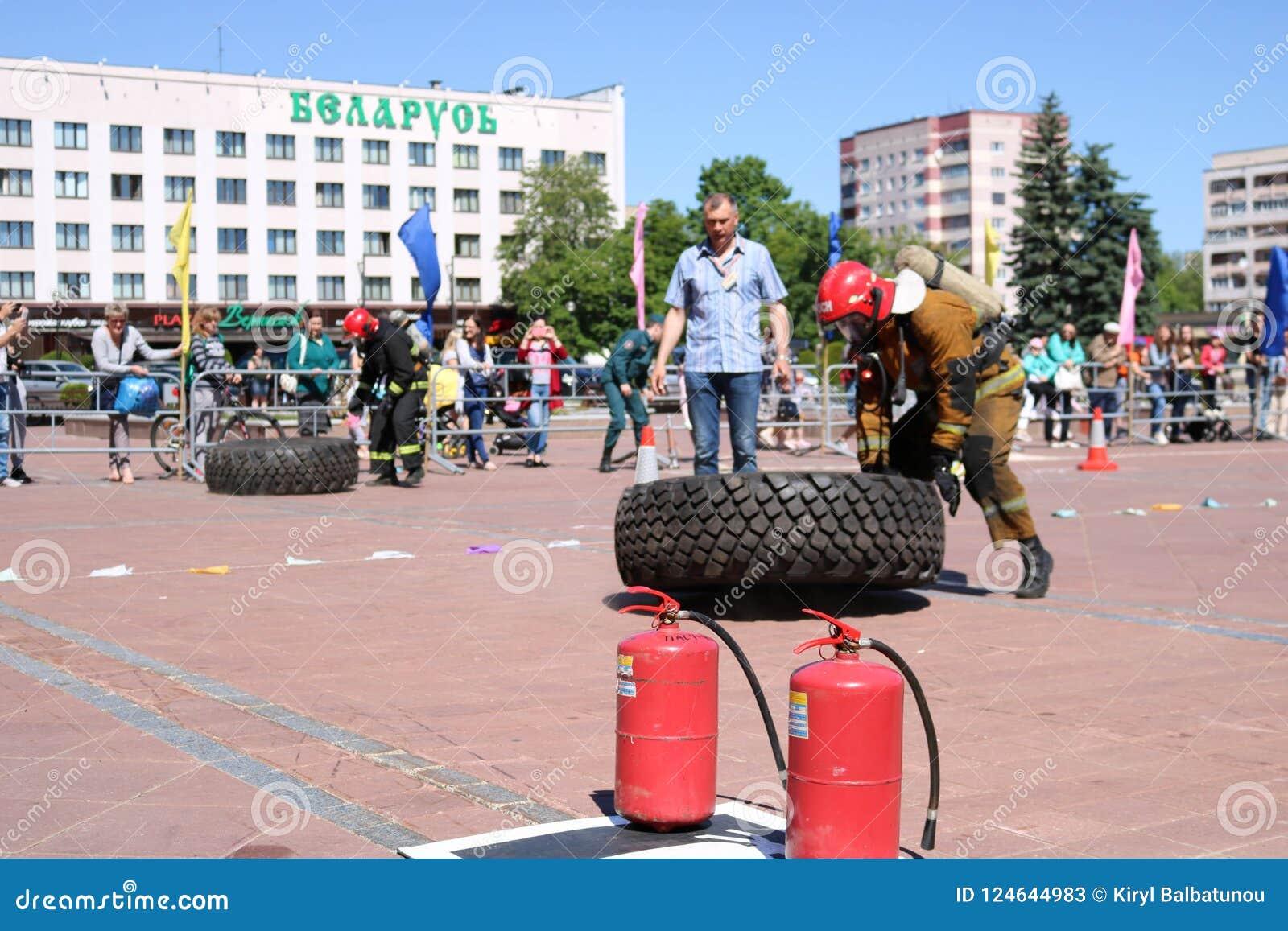 Palacz w fireproof kostiumu biega wielki gumowego i obraca toczy wewnątrz pożarniczego boju rywalizację, Białoruś, Minsk, 08 08 2