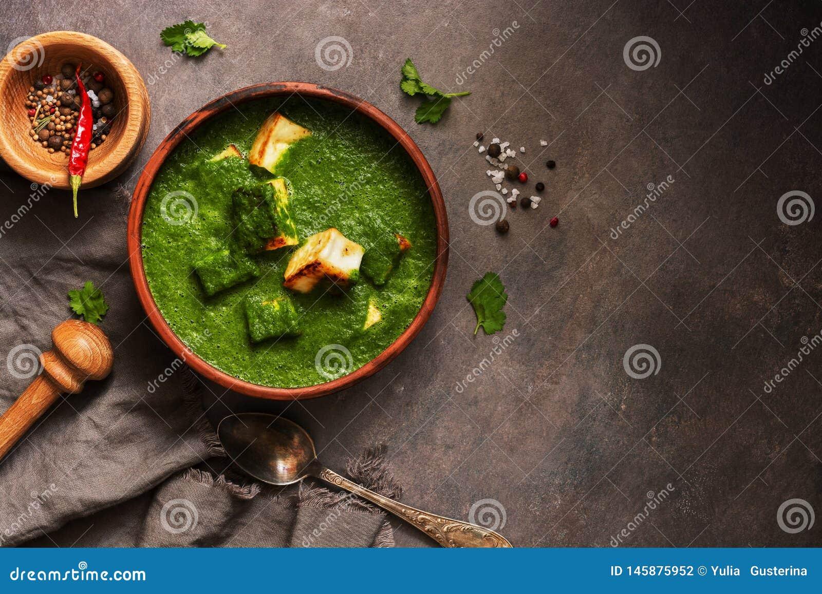 Palak paneer lub ser curry szpinaków i chałupy, moździerz z pikantność na ciemnym tle Tradycyjny India?ski naczynie Odg?rny widok