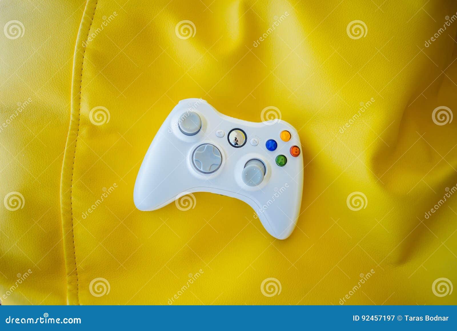 Palanca de mando blanca para la videoconsola en un fondo amarillo brillante Gamepad en un fondo de las sillas amarillas del bolso