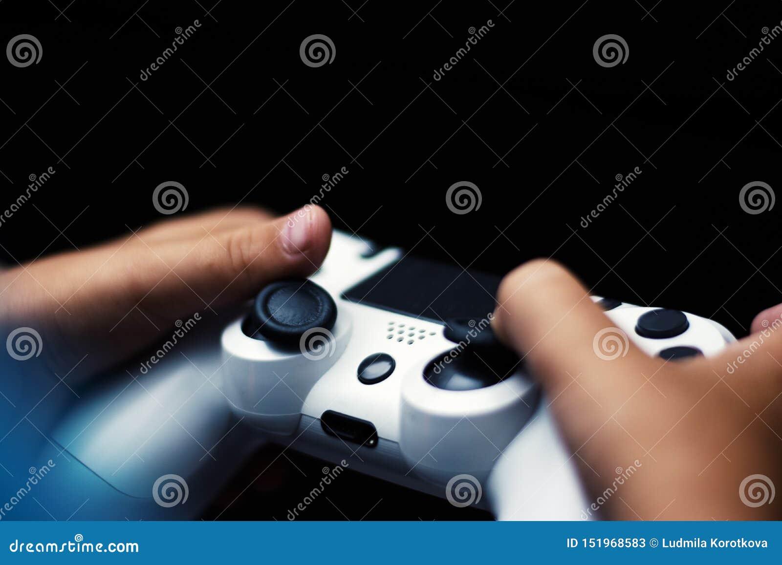 Palanca de mando en el juego aislado en negro Primer de las manos que llevan a cabo el gamepad en fondo negro