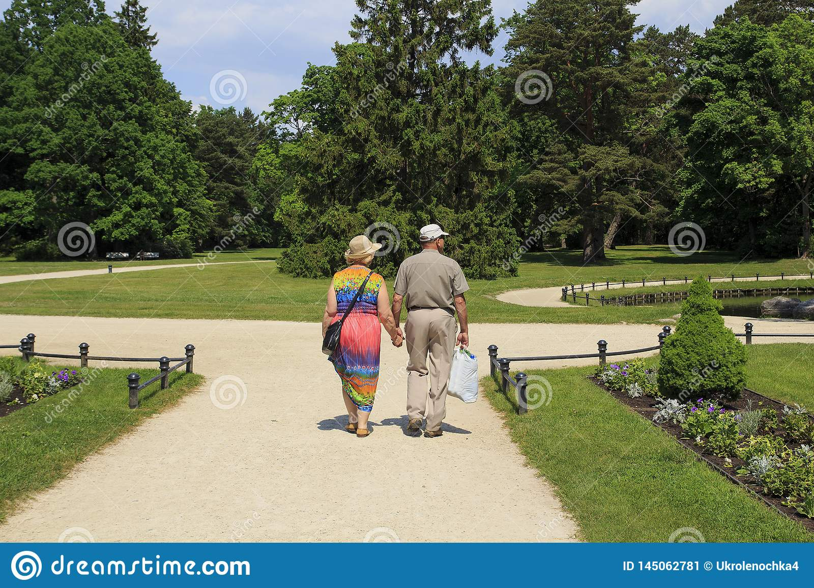 Palanga. Lithuania. May 31-2016 Rear view of senior couple walking down in park of the Amber museum