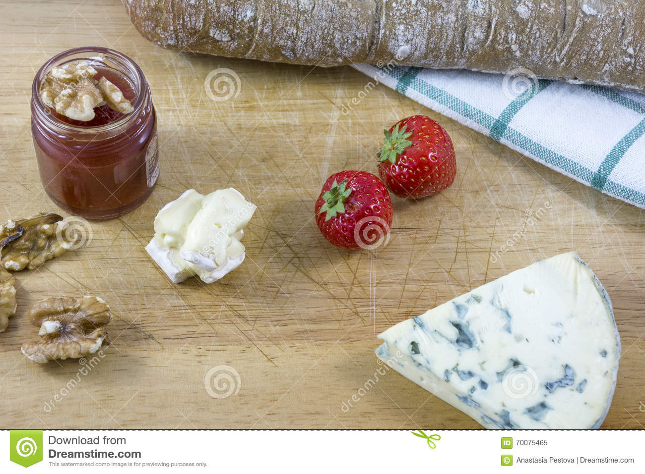 Palatable cheese roquefort and brie, bread, jam, nuts and strawberries as background