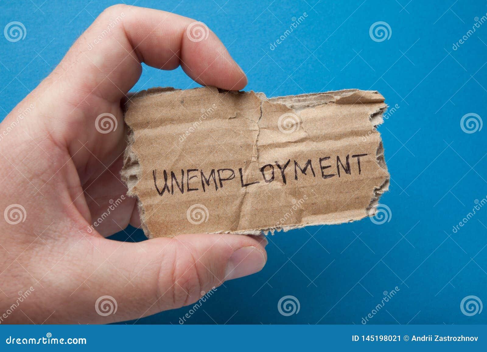 A palavra 'desemprego 'escrito no cartão na mão do homem, isolada em um fundo azul, desespero