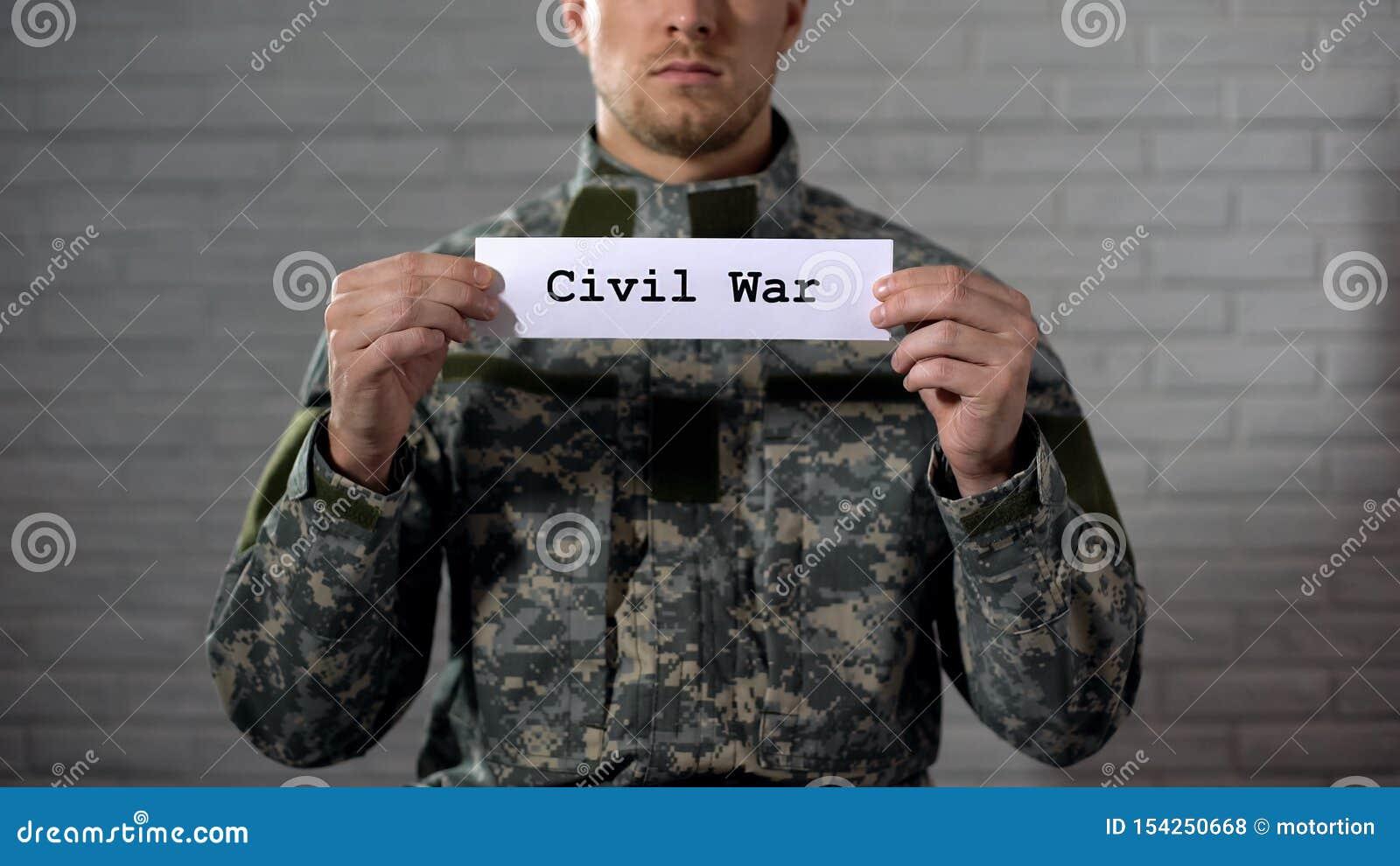 Palavra da guerra civil escrita nas mãos do sinal dentro do soldado masculino, da crueldade e da morte