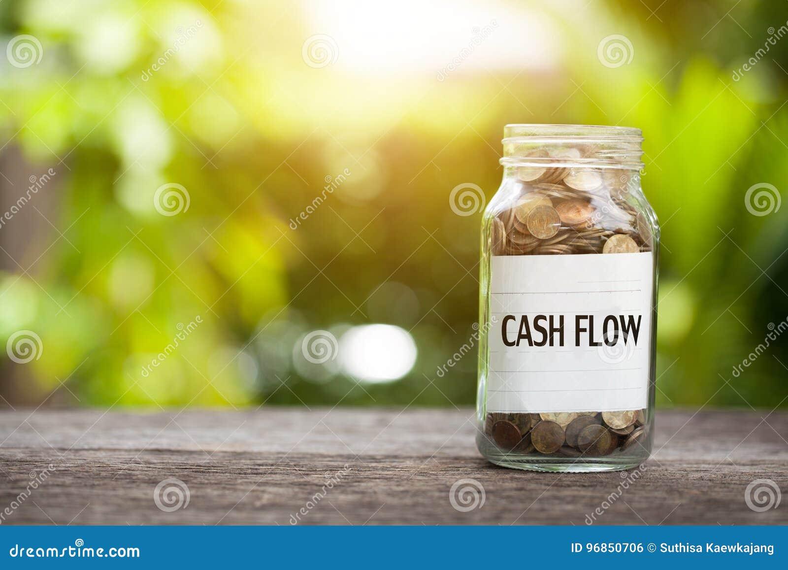 Palavra do fluxo de caixa com a moeda no frasco de vidro na tabela de madeira