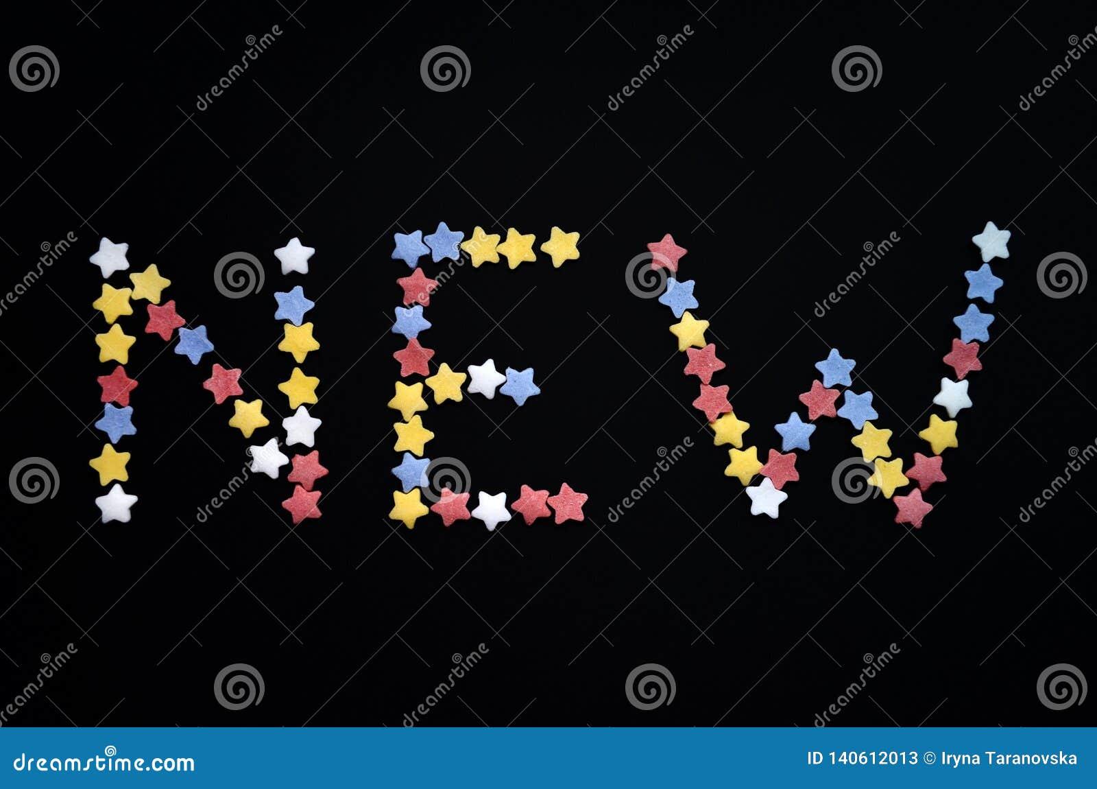 A palavra nova é escrita no tipo grosso de estrelas da pastelaria do açúcar em um fundo preto, para, propaganda, comércio, vendas