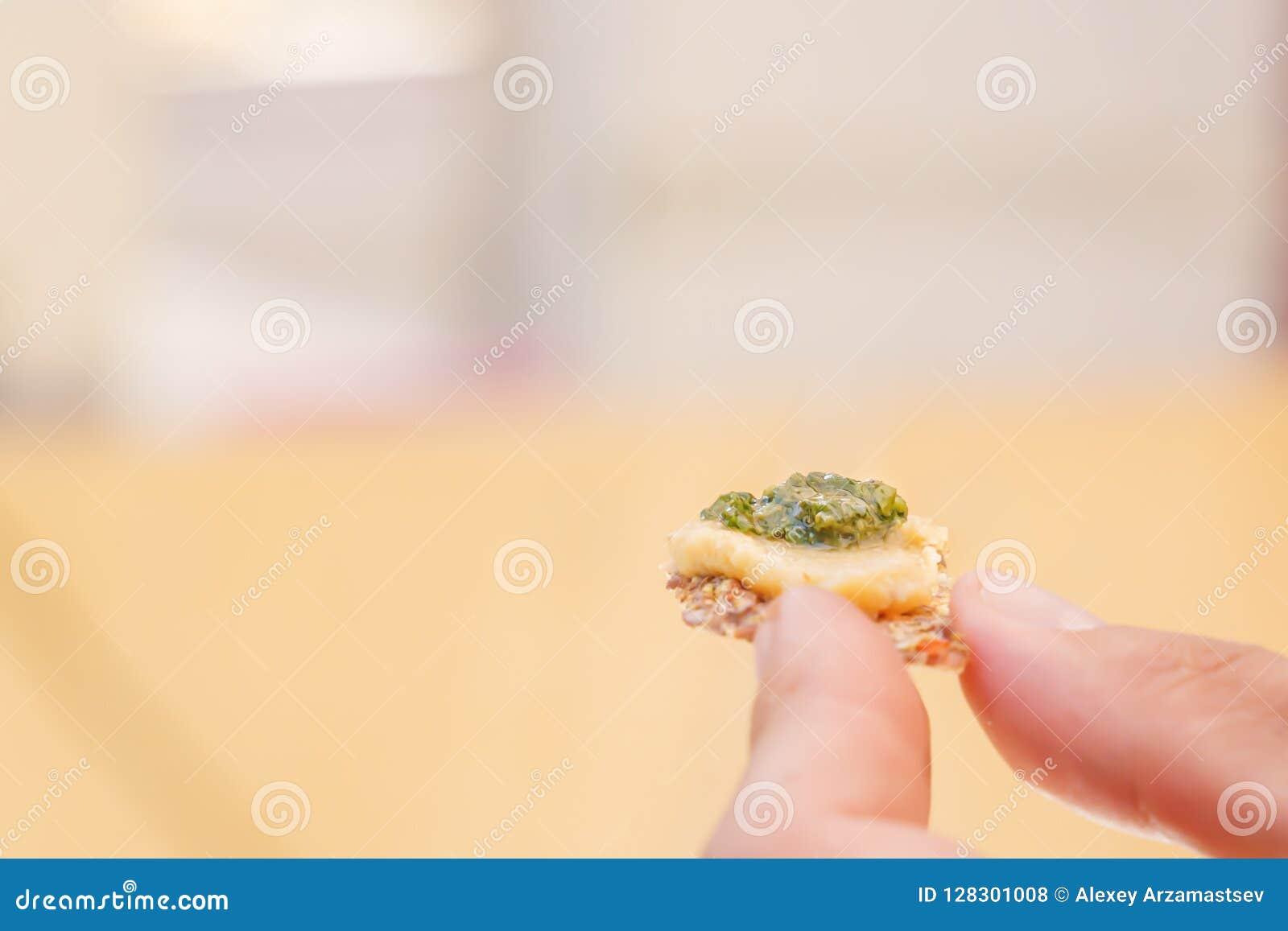 Palce trzymają plasterek chleb z śmietanką świeże zielenie Pożytecznie jarski posiłek