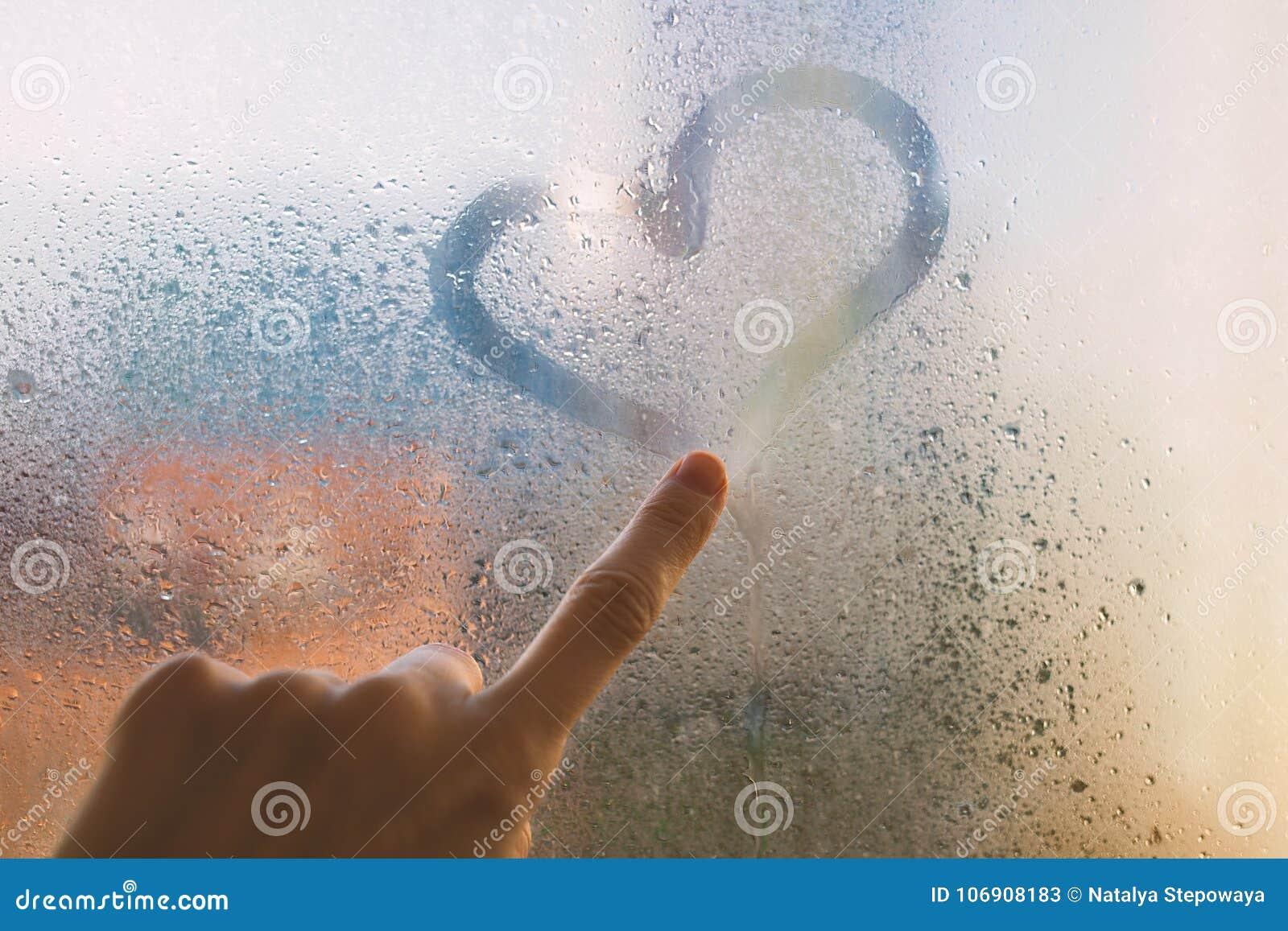 Palec na mokrym szkle rysuje serce