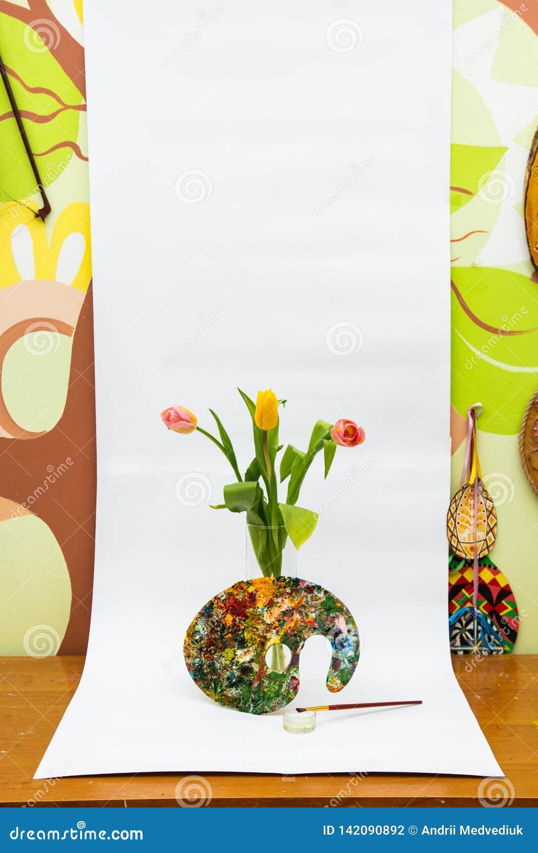 Paleta colorida da pintura a óleo com uma escova Escovas e pinturas de pintura para tirar Tulips em um fundo branco