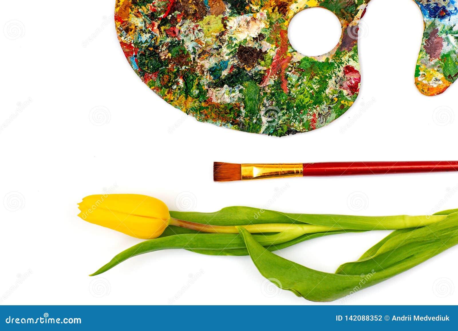 Paleta con las pinturas coloridas Paleta colorida de la pintura al óleo con un cepillo que alcanza adentro Tulipán en un fondo bl