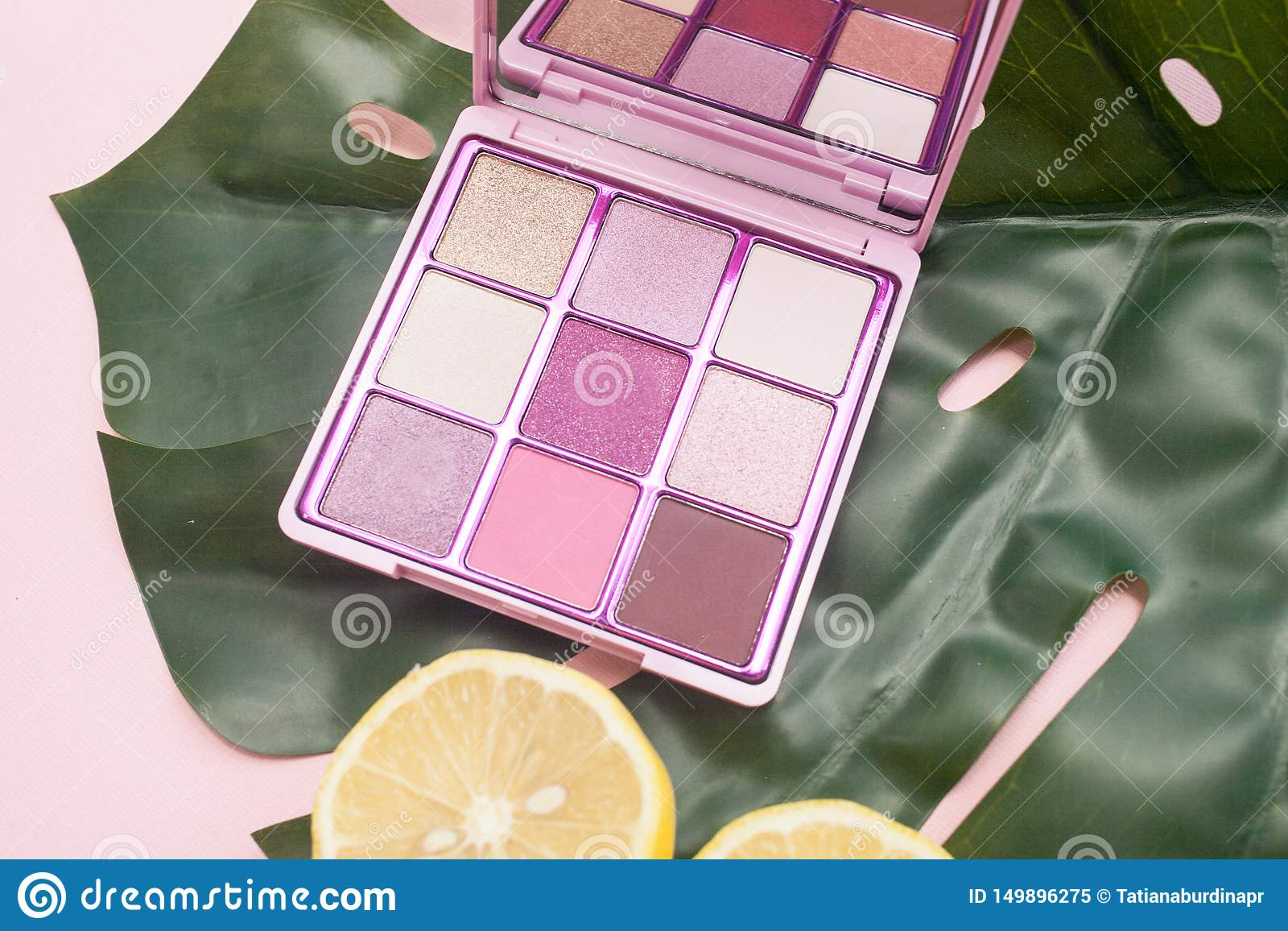 Paleta cuadrada del rosa y de sombras desnudas en un fondo rosado con la opinión de top verde de la hoja y del limón