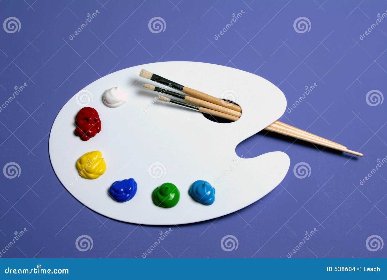 Paleta da pintura do artista com as pinturas e as escovas, simbólicas da arte