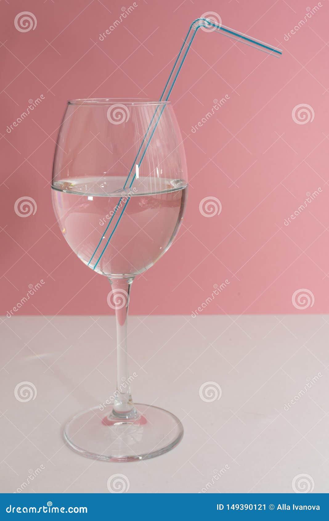 Palha bebendo azul no vidro de vinho completo com ?gua na tabela branca e no fim cor-de-rosa do fundo acima Espa?o da c?pia, moc